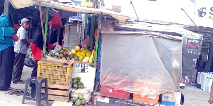 6일 서부자바 시장 상인이 마스크를 한 채 띠문 수리를 팔고 있다.jpg